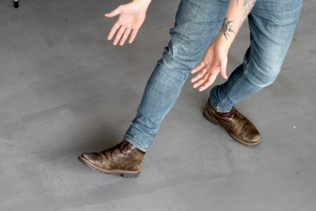 a man in jeans shows off his dashing boots, he is clearly very comfortable in his attire